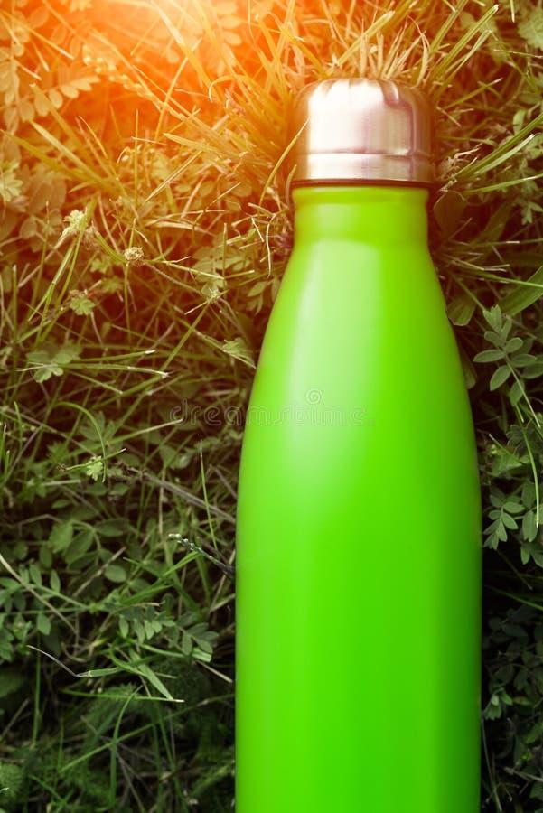Rostfri termosvattenflaska, ljus - grön färg Modell på bakgrund för grönt gräs med solljuseffekt royaltyfri bild