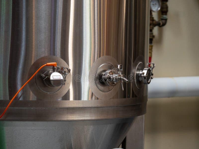 Rostfritt ståljäsningbehållare producera öl på ett bryggeri arkivbild