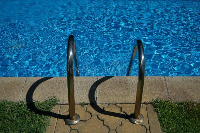 Rostfritt stålledstångtrappa av simbassängen med skuggor royaltyfri fotografi