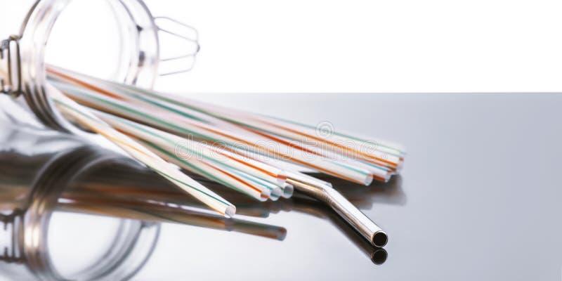 Rostfritt stålsugrör och plast- sugrör i glasflaska royaltyfri bild