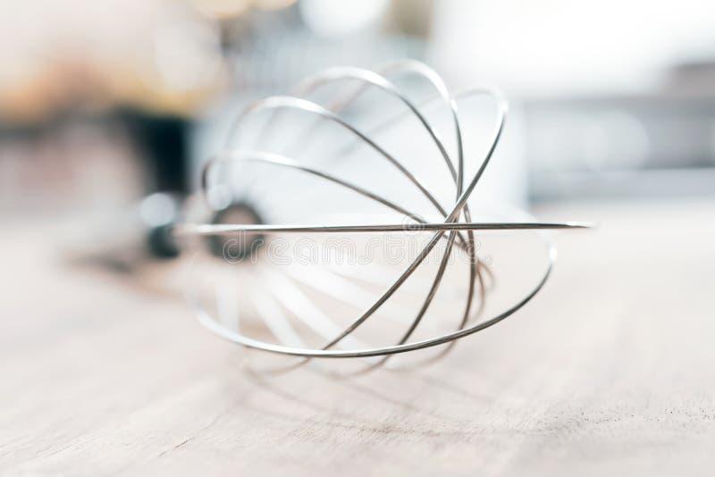 Rostfritt vifta på en trätabell med suddigt ut kökbakgrund arkivbilder