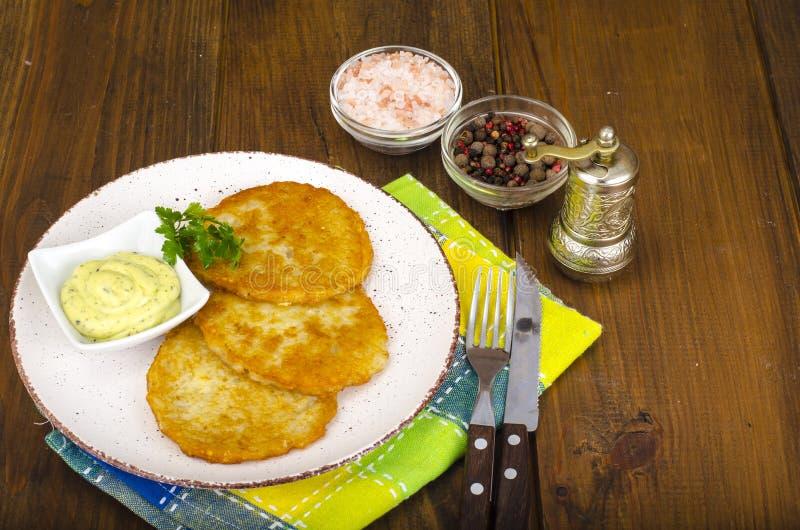 Rosti vegetal, crepes de patata fritas de oro con las inmersiones de la coliflor y crema agria foto de archivo libre de regalías