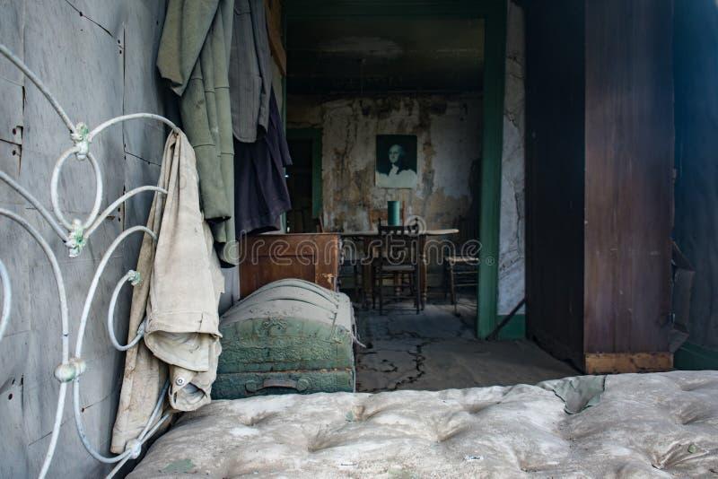 Rostig bedframe och madrass inom ett hem i Bodie Ghost Town i Kalifornien arkivbild