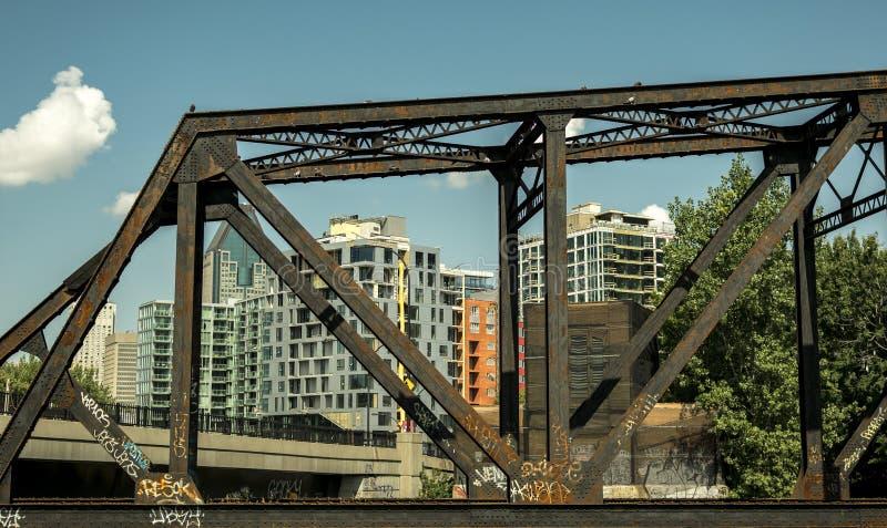 Rostig bro med byggnader i bakgrunden royaltyfria foton