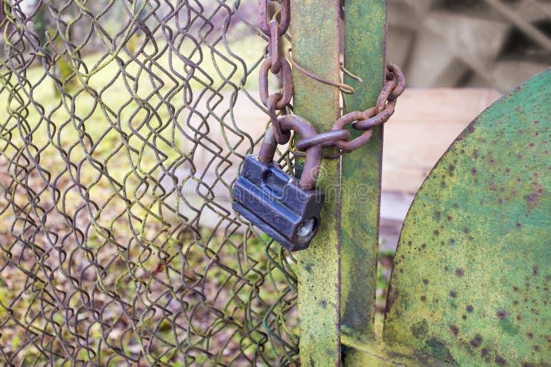 Rostig gammal hänglås och kedja på ett grönt staket arkivbild