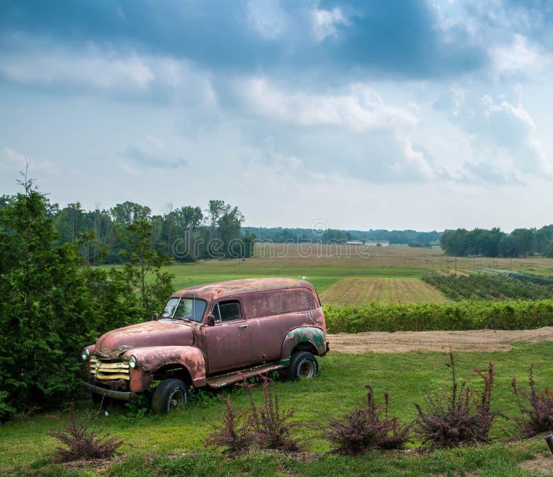 Rostig gammal panellastbil i ett lantgårdfält royaltyfri fotografi