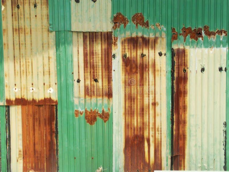 Rostig gräsplan målad metallvägg med sprucken målarfärg, texturfärg royaltyfri fotografi