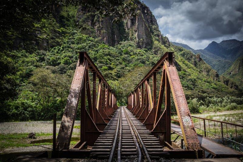Rostig järnvägsbro över floden med att omge för berg royaltyfria bilder