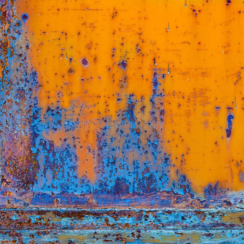 Rostig målad metall med sprucken målarfärg Apelsin- och blåttfärger arkivbild