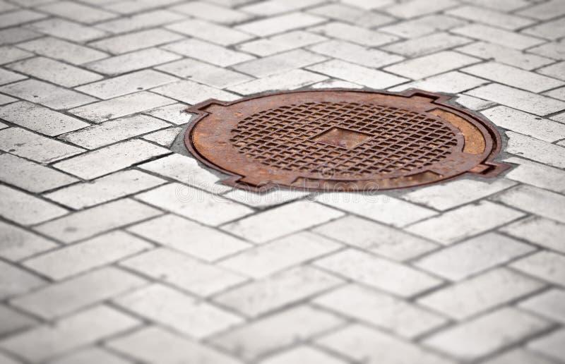 Rostig manhole i trottoaren royaltyfri bild
