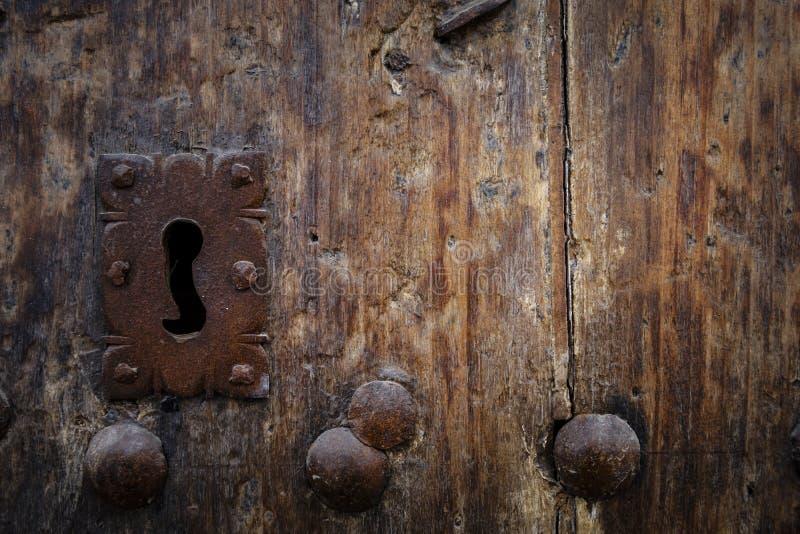 Rostig nyckelhål i gammal trädörr royaltyfri foto