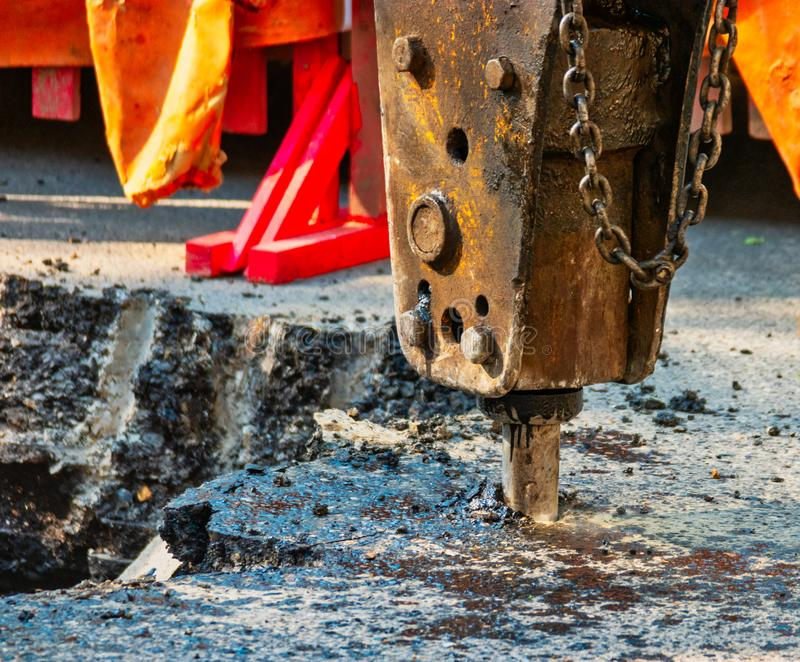 Rostig pneumatisk jagare som arbetar på asfaltyttersida - repairmentarbeten royaltyfria foton