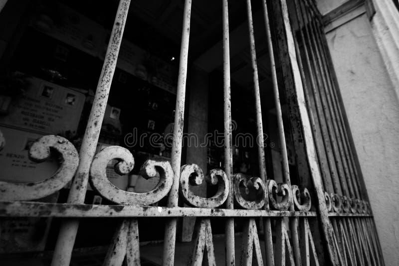 Rostig port med gravstenar i kyrkogård arkivbilder