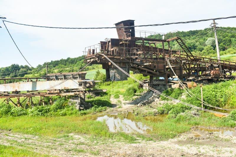 Rostiga enorma maskiner i övergiven kolgruva Förfall för tung bransch i Rumänien arkivbild