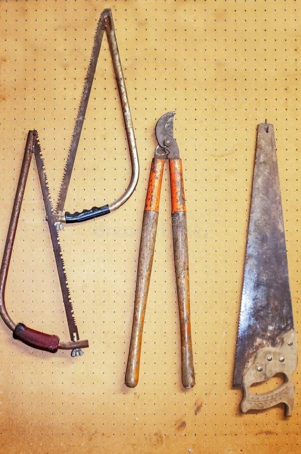 Rostiga gamla hjälpmedel som hänger på en pegboard i ett bostads- garage inklusive sågar och en lemskärare arkivbilder