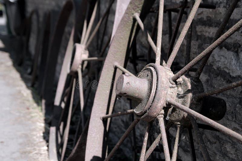Rostiga gamla lantgårdvagnshjul lutade upp mot en lantlig stenvägg royaltyfria bilder