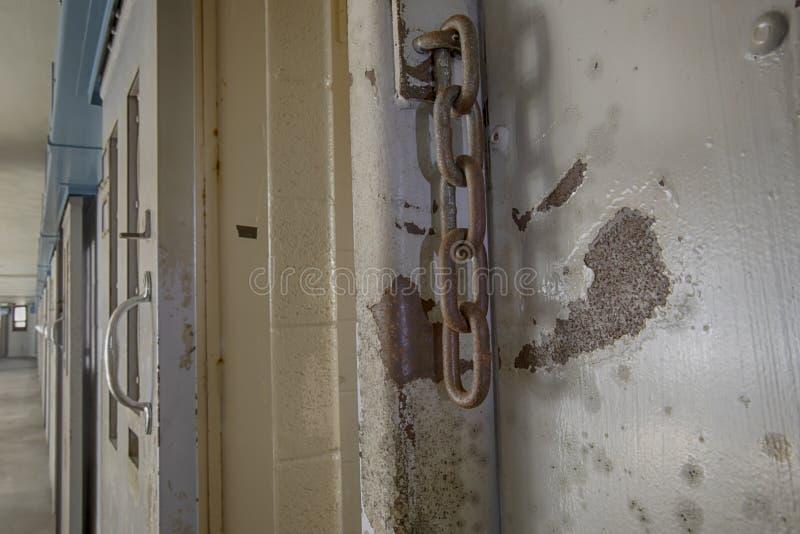 Rostiga kedjor på dörr för fängelsecell fotografering för bildbyråer