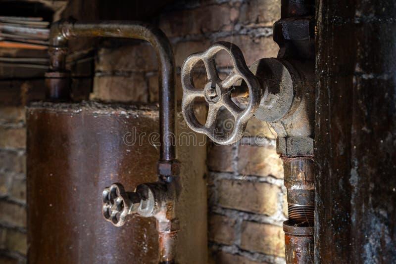 Rostiga rör för kokkärlrum Gammal metallkokkärl som frambringar uppvärmning och levererar den för att returnera till och med rörl royaltyfri bild