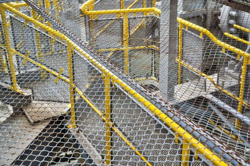 Rostiga staket över gula räcke arkivbild