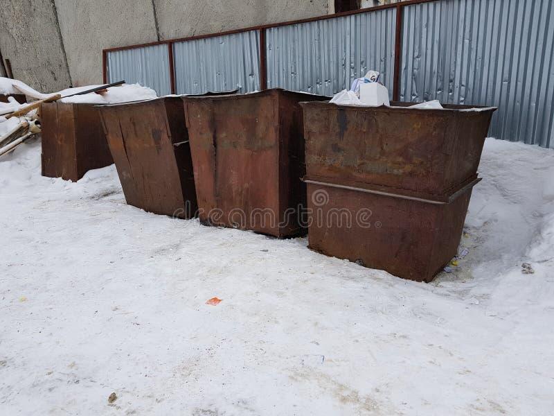 Rostige Abfalleimer auf dem Schnee im Winter stockfotografie
