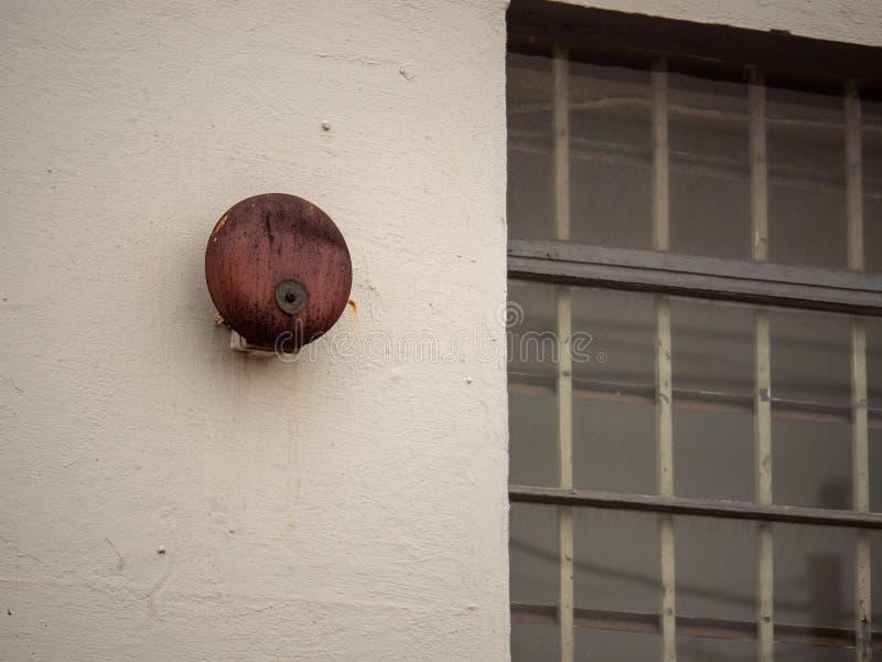 Rostige Alarmglocke, die außerhalb des großen Fensters außerhalb des Schulgebäudees hängt lizenzfreies stockfoto