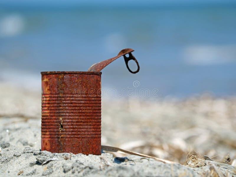 Rostige Blechdose auf dem Strand mit blauem Meer lizenzfreie stockbilder