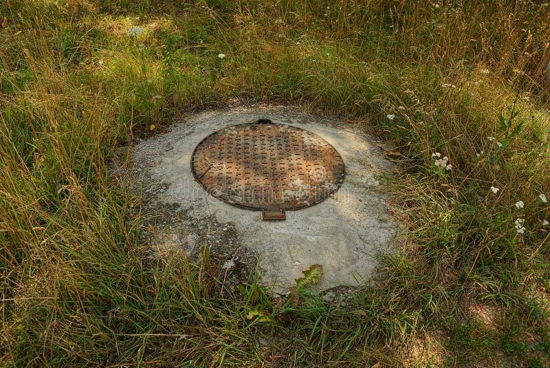 Rostige Entwässerungsluke Browns im grauen Beton im Gras und in der Vegetation im Park stockbilder