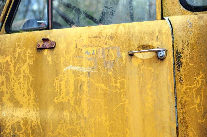 Rostige gelbe Autotür mit der Schale der Farbe stockbilder