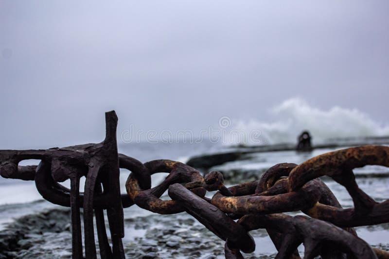 Rostige Kette am Pier des dunklen Meeres stockbilder