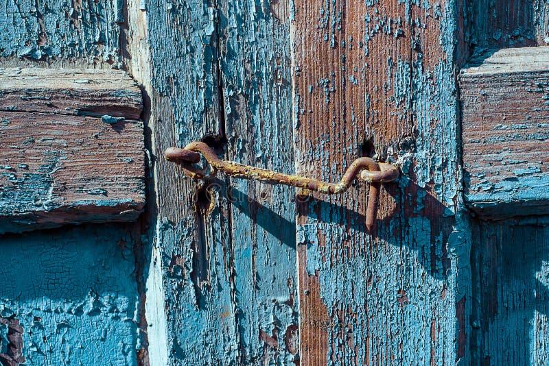 Rostige Metallklinke auf dem hölzernen blauen Fensterladen gebrochen und Kratzer Horizontale Schmutzbeschaffenheit der Nahaufnahm stockbilder