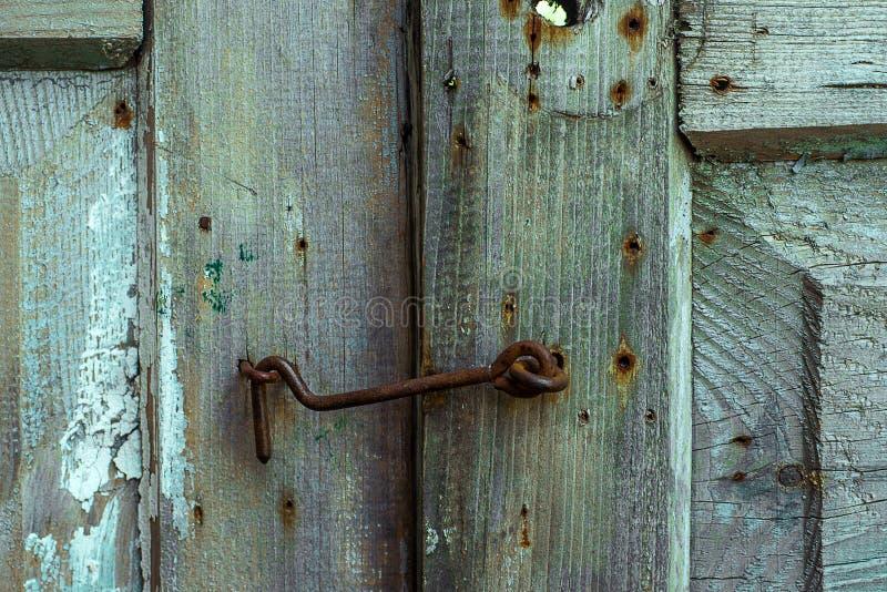Rostige Metallklinke auf dem hölzernen grünen Fensterladen gebrochen und Kratzer Horizontale Schmutzbeschaffenheit lizenzfreie stockfotografie