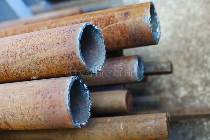 Rostige Metallrohre verschiedene Durchmesser liegen auf dem konkreten Boden Industrieller Hintergrund stockfotos