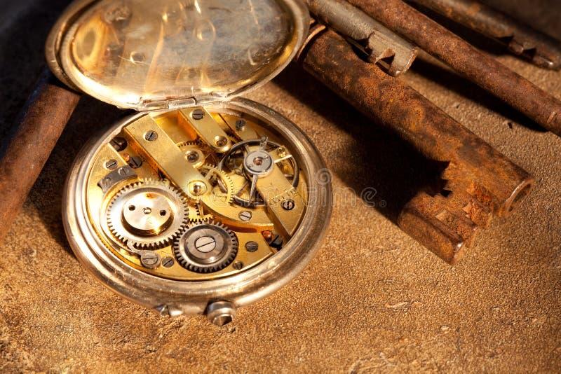 Rostige Tasten und Taschenuhr stockbild