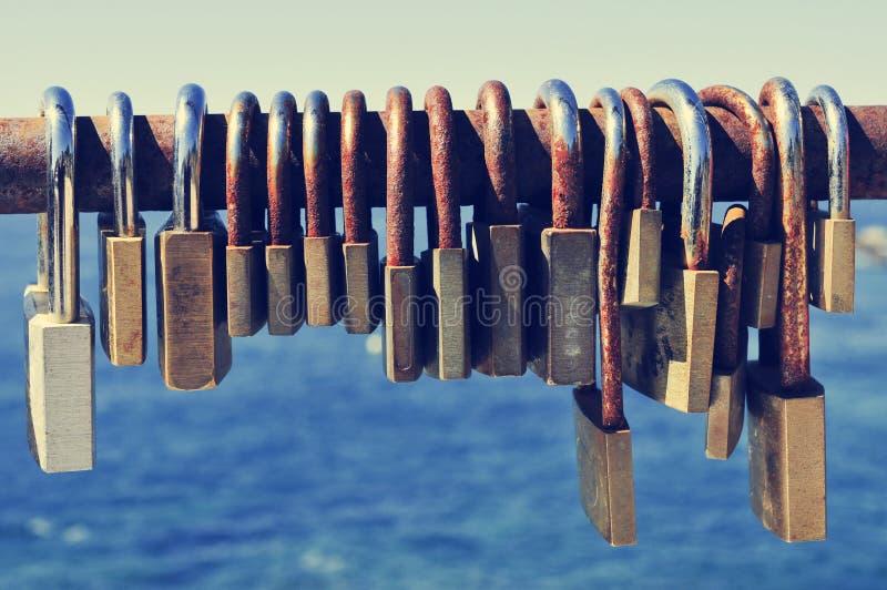 Rostige Vorhängeschlösser auf einem Geländer nahe dem Meer stockbilder