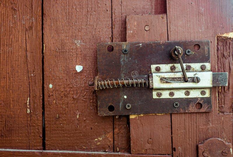 Rostiger alter geheimer Verschluss auf roter hölzerner Tür mit gebrochenem und Kratzer Horizontale Schmutzbeschaffenheit stockfotografie