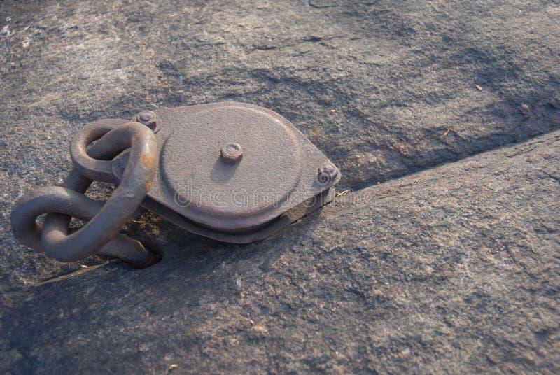 Rostiger Flaschenzug verankert in einem Felsen stockbild