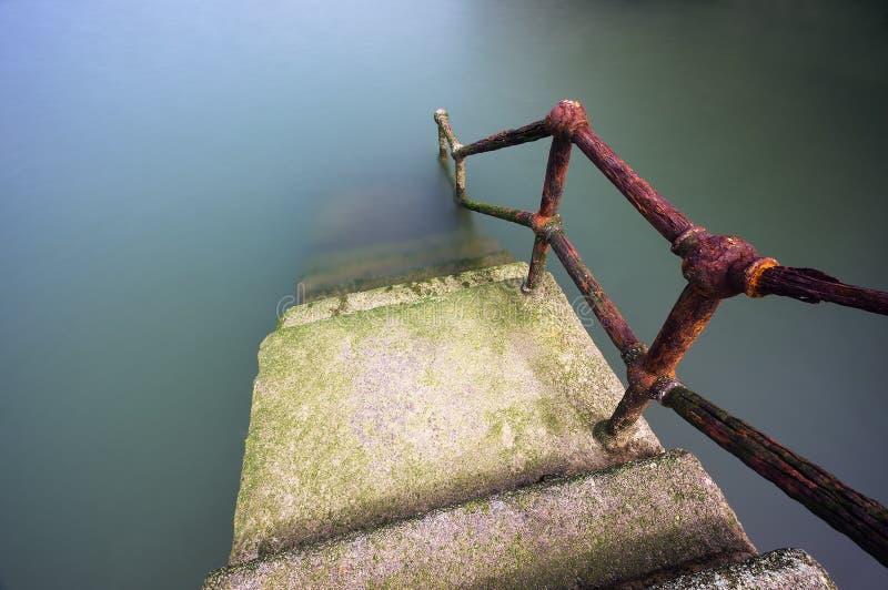 Rostiger Handlauf, der unten auf Wasser geht stockfoto