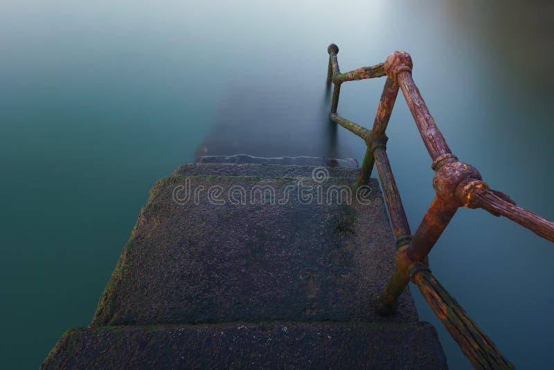 Rostiger Handlauf, der unten auf Wasser geht lizenzfreie stockfotografie