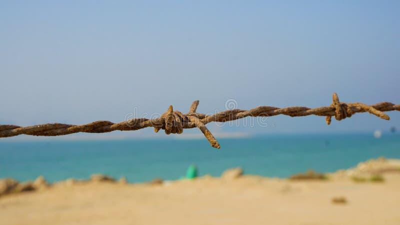 Rostiger Stacheldraht, der felsigen Strand vom Zugang trennt stockfoto