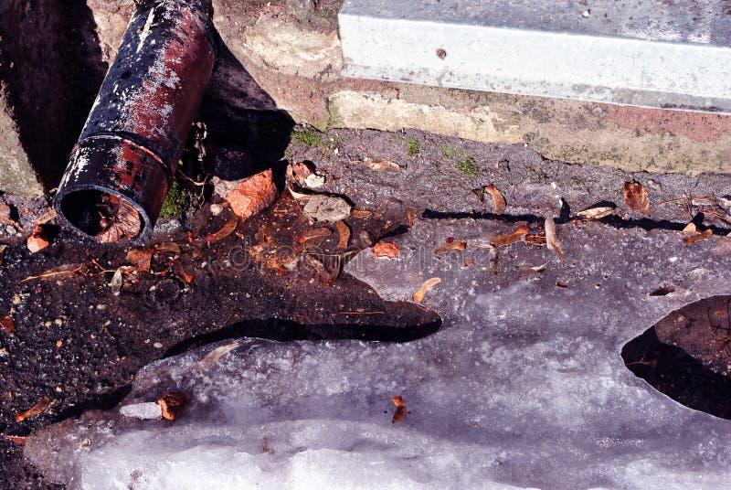 Rostiges Abflussrohr, Wassertropfen von ihm, trockene Ahornblätter, Lindesamen und schmelzendes Eis auf dunkler Asphalthintergrun stockfoto