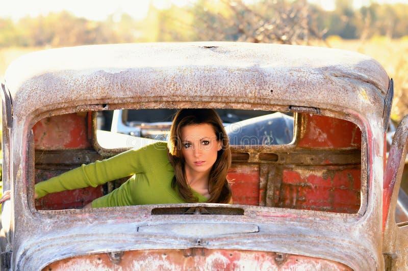 Rostiges altes Automobil mit junger Frau nach innen lizenzfreie stockfotografie