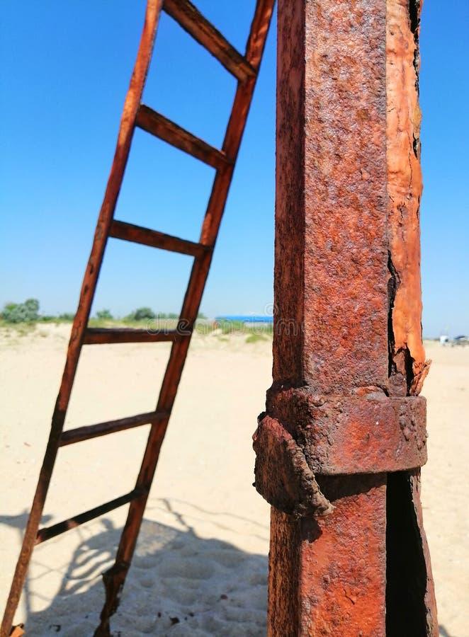 Rostiges Eisen und Treppe auf dem Sand stockfoto