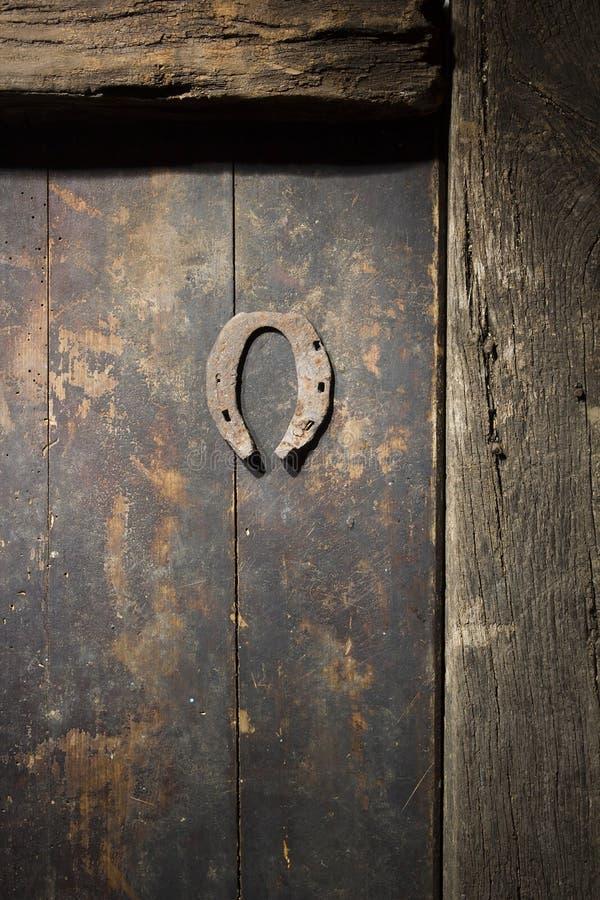 Rostiges Hufeisen auf der alten Tür lizenzfreies stockbild