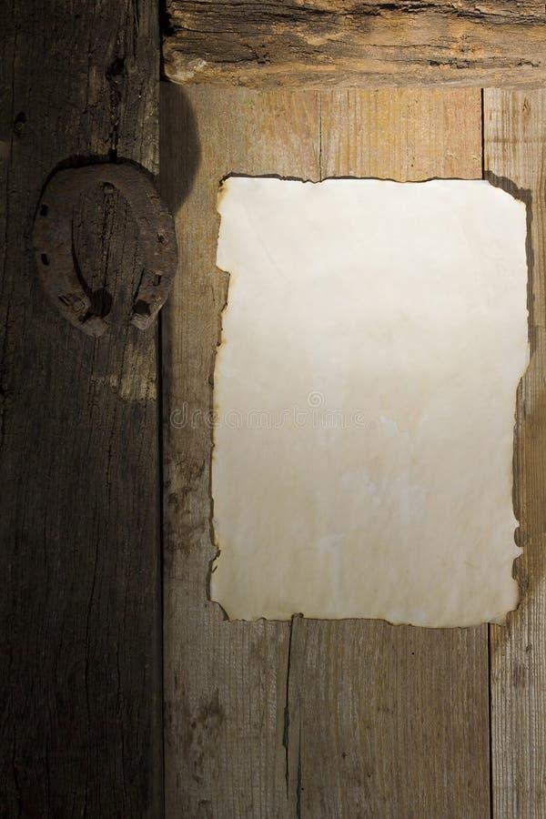 Rostiges Hufeisen und ein Blatt Papier auf der Tür stockbild