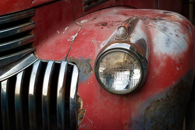 Rostiges rotes LKW-Auto der Weinlese mit einem neuen Scheinwerfer, Weichzeichnung lizenzfreies stockfoto