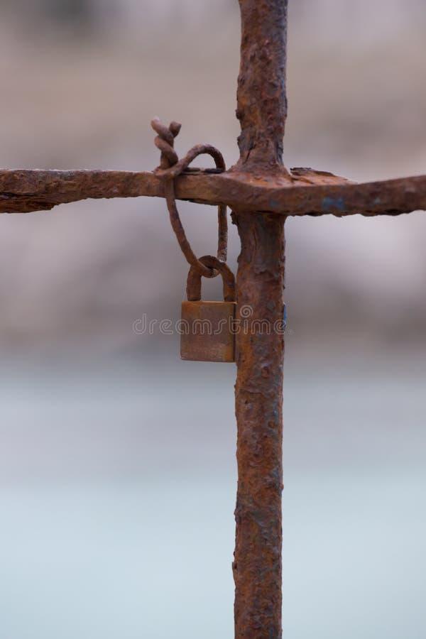 Rostiges Vorhängeschloß befestigt zu einem Tor stockbild