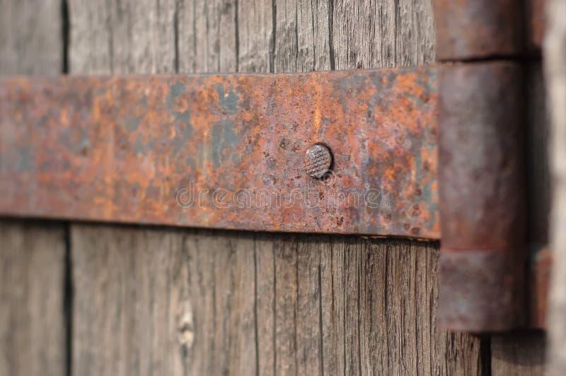 Rostigt gångjärn och fragment av grunt djup för gammal trädörr av fältet arkivfoton