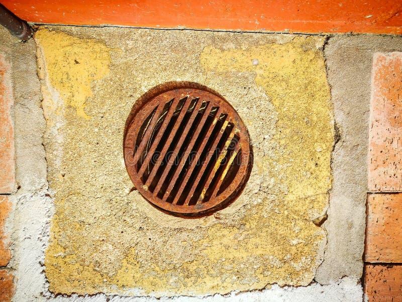 Rostigt gammalt hål för cirkelvattenavrinning på trottoar royaltyfri foto