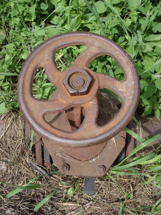 Rostigt stålvattenklapp i det gröna och torra gräset fotografering för bildbyråer