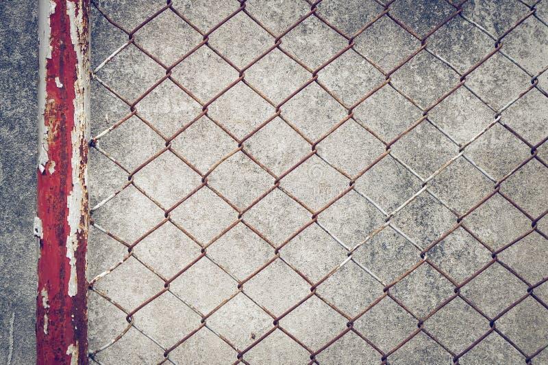 Rostigt staket för järnkedjetråd på cementväggen royaltyfri fotografi